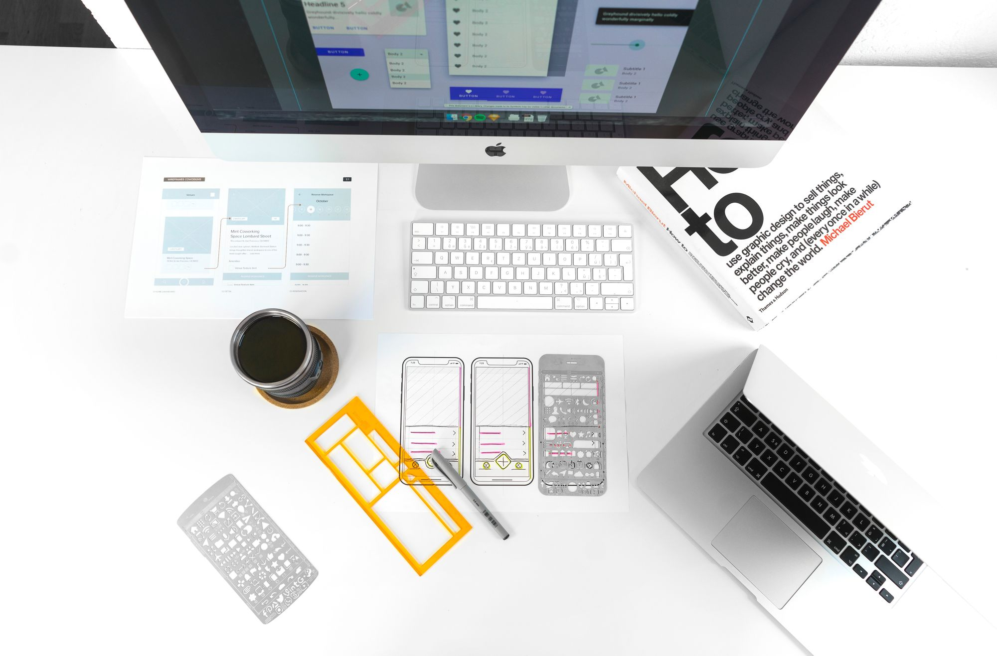 White desk with laptop, wireframe stensils and coffee and other UX tools